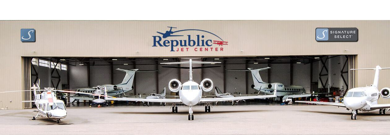 White airplanes, jets, and helicopters parked in a small airport garage
